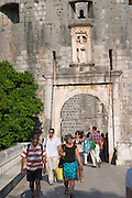 The city gate Pile west entrance with tourists and with Carved stone statue of the patron saint St Blaise above and guarding the Vrata Pile city gate Dubrovnik, old city. Dalmatian Coast, Croatia, Europe.