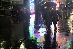 October 10, 2018 - Kolkata, West Bengal, India - People hold umbrella and cross the street to protect them from rain due to cyclone Title as the street decorated with lights ahead of Durga Puja festival. Rain is started due cyclone Title over Bay of Bengal as the streets are decorated with lights ahead of Durga Puja festival. (Credit Image: © Saikat Paul/Pacific Press via ZUMA Wire)