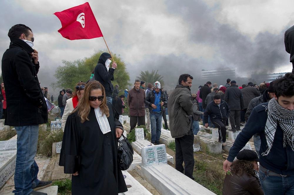 Cimetiere Jallez, la foule essaye d'echapper au tires de gaz lacrymogene. l'hommage du peuple Tunisien à Chokri Belaid fut perturbé par incidents entre jeunes casseurs et la police anti-emeutes. Des voitures sont brulées.