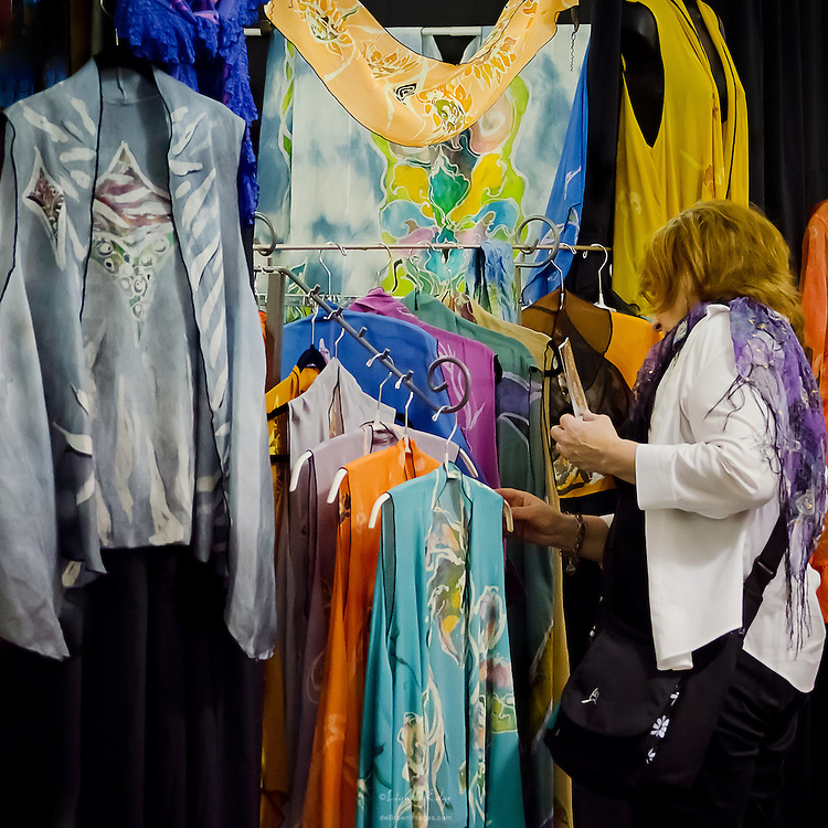 A visitor to Wheaton Arts' 2012 Fine Craft Fair browses through a vendor's fabric and textile choices.