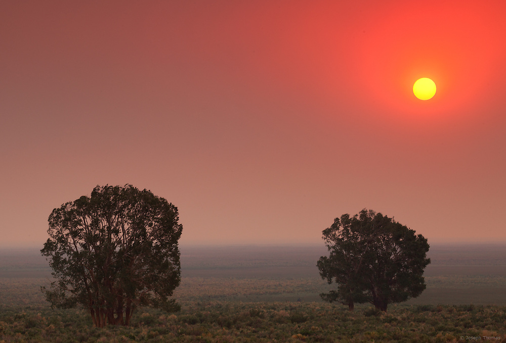 Smoke from a nearby forest fire casts the San Luis Valley in an eerie crimson haze as the disc of the sun descends toward the horizon.