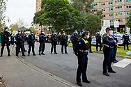 Specialist public order police stand guard at the entrance of 120 Racecourse Road amid the third full day of the total lockdown of 9 housing commission high rise towers in North Melbourne and Flemington during COVID 19.After recording 191 COVID-19 cases overnight forcing Premier Daniel Andrews to announce today that all of metropolitan Melbourne along with one regional centre, Mitchell Shire will once more go back to stage three lockdowns from midnight Wednesday June 8. This comes as the residents of the housing commission towers in North Melbourne and Flemington finish their third day under extreme lockdown, despite only 27 cases being found in the towers. Members of the public gathered outside of the towers this afternoon in support of those trapped inside while riot police arrested two women for standing too close to the fence. While the women were later released, tensions are boiling over both in the towers and out. With 772 active cases in Victoria, NSW closed their border to Victoria effective at midnight tonight.