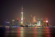 The night lights of the Shanghai Financial District glow eerily through the air pollution that cloaks the city