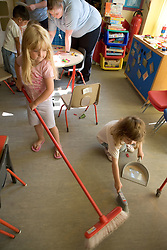 Nursery School girls sweeping up their classroom after an art lesson,