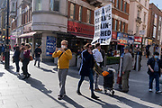 A young man stands near Leicester Square holding a religious message telling the public to wake up, they are being brainwashed by Satan, on 12th October 2021, in London, England.