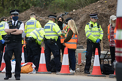 Enfield, UK. 15th September, 2021. A Metropolitan Police officer arrests an Insulate Britain climate activist who had blocked a slip road from the M25 at Junction 25 as part of a campaign intended to push the UK government to make significant legislative change to start lowering emissions. The activists, who wrote to Prime Minister Boris Johnson on 13th August, are demanding that the government immediately promises both to fully fund and ensure the insulation of all social housing in Britain by 2025 and to produce within four months a legally binding national plan to fully fund and ensure the full low-energy and low-carbon whole-house retrofit, with no externalised costs, of all homes in Britain by 2030 as part of a just transition to full decarbonisation of all parts of society and the economy.