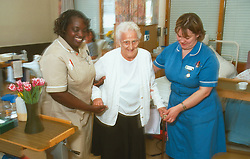 Female nurse and nursing auxiliary assisting elderly woman to walk,
