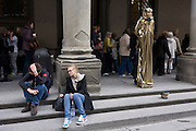 Tired and disappointed tourists and a pretend Egyptian pharaoh busker stand awaiting custom in Florence's Piazza degli Uffizi. In the darker covered galleries and streets around Florence's Uffizi galleries, the two young visitors sit looking exhausted and disillusioned, also possibly overwhelmed by the amount of culture and art in this renaissance city. The Uffizi Gallery is one of the oldest and most famous art museums of the Western world. It is housed in the Palazzo degli Uffizi, a palazzo in Florence, Italy.