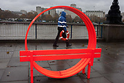 A security employee working for Londons Southbank carries a life ring coincidentally passing through circular artwork overlooking the River Thames, on 21st November 2016, Southbank, London, England.