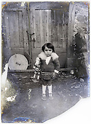 little girl posing with toy horse early 1900s