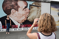 Tourist taking photograph of The Kiss mural painted on original section of Berlin Wall at East Side gallery in Berlin, Germany ...Editorial Use Only