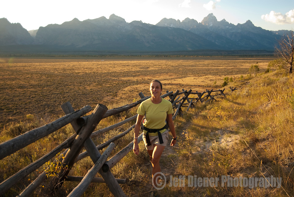A young woman hikes along a fenceline in Grand Teton National Park, Jackson Hole, Wyoming.