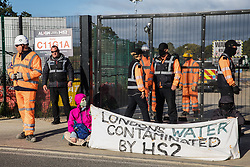Environmental activists from HS2 Rebellion sit in the road holding a banner to block a gate providing access to a site for the HS2 high-speed rail link on 12 September 2020 in Harefield, United Kingdom. Anti-HS2 activists continue to try to prevent or delay works on the controversial £106bn HS2 high-speed rail link in the Colne Valley where thousands of trees have already been felled.