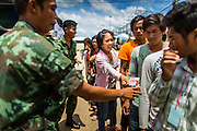09 JULY 2014 - ARANYAPRATHET, SA KAEO, THAILAND: A Cambodian migrant worker passes another migrant Thai currency so he can pay for his temporary ID card at the Thai Immigration One Stop Service Center in Aranyaprathet on the Thai-Cambodian border. The temporary ID cards cost 40 Baht, about $1.30 (US). More than 200,000 Cambodian migrant workers, most undocumented, fled Thailand in early June fearing a crackdown by Thai authorities after a coup unseated the elected government. Employers have been unable to fill the vacancies created by the Cambodian exodus and the Thai government has allowed them to return. The Cambodian workers have to have a job and their employers have to vouch for them. The Thai government is issuing temporary ID cards to allow them to travel openly to their jobs. About 800 Cambodian workers came back to Thailand through the Aranyaprathet border crossing Wednesday. The Thai government has opening similar service centers at three other crossing points on the Thai-Cambodian border.    PHOTO BY JACK KURTZ