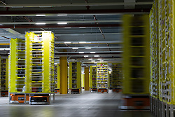 """© Licensed to London News Pictures . 04/12/2019. Manchester , UK . Robotic stock trucks shift products around a central unit within the warehouse . Inside the """"MAN1"""" Amazon fulfilment centre warehouse at Manchester Airport in the North West of England . Photo credit : Joel Goodman/LNP"""
