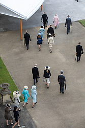 Queen Elizabeth II and the Duke of Edinburgh (both top centre) lead members of the Royal family to greet guests at a garden party at Buckingham Palace in London.