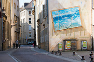A man holds the hands of two young boys as they walk down a street in Metz, France. A large painting is on one side of a building