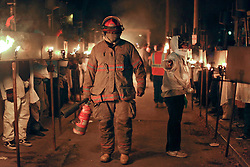 13 Feb 2015. New Orleans, Louisiana.<br /> Mardi Gras. Krewe D'Etat prepares to make its way along Magazine Street. A fireman walks amidst the flambeaux walkers as they prepare for the parade.<br /> Photo; Charlie Varley/varleypix.com