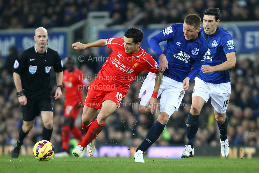 Philippe Coutinho of Liverpool gets away from James McCarthy and Gareth Barry of Everton. Barclays Premier league match, Everton v Liverpool at Goodison Park in Liverpool, Merseyside on Saturday 7th February 2015<br /> pic by Chris Stading, Andrew Orchard sports photography.