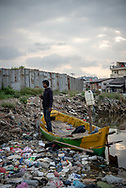 Jakarta, Indonesia - July 9, 2017: Trash, including plastic bottles and bags, pollutes a waterway in Jakarta, Indonesia. A man holding a cigarette stands in a small boat waiting for approaching passengers he will ferry to the opposite side.