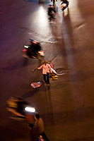 Street vendors with their baskets walking along the road amongst the traffic.