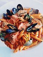 A beautiful plate of mussel, salmon, and clam pasta.