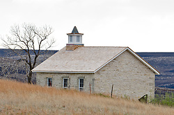 Recently burned prairie seen in the background is contrasted with unburned prairie grass in this photo of the Lower Fox Creek School, a one-room schoolhouse located in the Tallgrass Prairie National Preserve. Prairie grasses are burned in the spring to help maintain a healthy tallgrass prairie ecosystem and prepare the land for cattle grazing Tallgrass Prairie National Preserve is the only unit of the National Park Service dedicated to the preservation of the tallgrass prairie ecosystem. The Tallgrass Prairie National Preserve is co-managed with The Nature Conservancy. The 10,894-acre preserve is located in the Flint Hills of Kansas in Chase County near the towns of Strong City and Cottonwood Falls. NOTE: A comparison of the burned area of this photo with an two-month later photo of the prairie growing back is available. See photo id# I0000s35tbY0nhE8