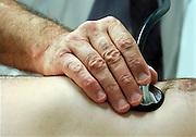 Nederland, Nijmegen, 3-11-2005..Een arts, huisarts, specialist, luistert met een stethoscoop, stethoskoop naar de hartslag, het hart, van een manlijke patient. Keuring, wao, wia, hart en vaatziekte, hartenvaatziekte, hartritme, hartaandoening, hartfalen, hartaanval, hartinfarct, conditie, konditie lichaam, gezondheidszorg, onderzoek...Foto: Flip Franssen