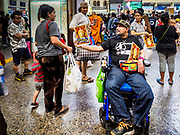 "11 APRIL 2017 - BANGKOK, THAILAND: A man in a wheelchair hands out photos of Bhumibol Adulyadej, the Late King of Thailand, as Songkran holiday travelers walk into Hua Lamphong train station in Bangkok. Songkran is the traditional Thai Lunar New Year. It is celebrated, under different names, in Thailand, Myanmar, Laos, Cambodia and some parts of Vietnam and China. In most places the holiday is marked by water throwing and water fights and it is sometimes called the ""water festival."" This year's Songkran celebration in Thailand will be more subdued than usual because Thais are still mourning the October 2016 death of their revered Late King, Bhumibol Adulyadej. Songkran is officially a three day holiday, April 13-15, but is frequently celebrated for a full week. Thais start traveling back to their home provinces over the weekend; busses and trains going out of town have been packed.     PHOTO BY JACK KURTZ"