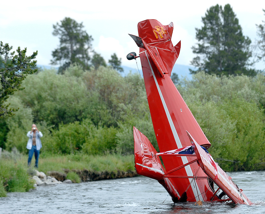 NEWS&GUIDE PHOTO / PRICE CHAMBERS.A bi-plane crashed by pilot Brent Blue sits in Fish Creek on Tuesday afternoon after he tried to abort his take off from an earthen airfield near Wilson. Neither Blue or his passenger Laurie Blann were injured and both made it to dry land quickly after the accident.