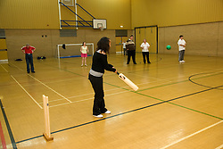 Day service users with learning disability playing indoor cricket in the gym,