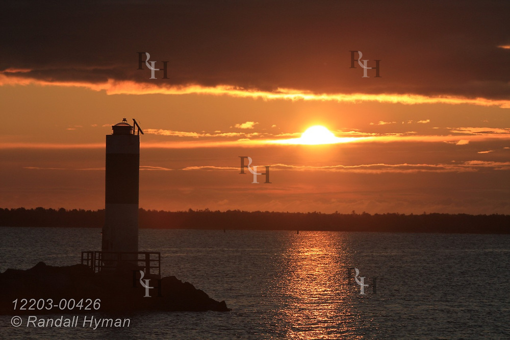 Lake Huron sunrise backlights lighthouse and breakwater on a September morning in Alpena, Michigan.