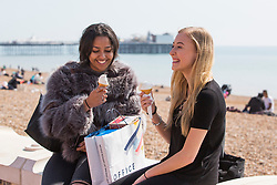 © Licensed to London News Pictures. 06/04/2017. Brighton, UK. 17 year olds JESS and SOPHIE from Essex enjoy an ice-cream on Brighton promenade as sunny and warm weather is hitting the seaside resort. Photo credit: Hugo Michiels/LNP