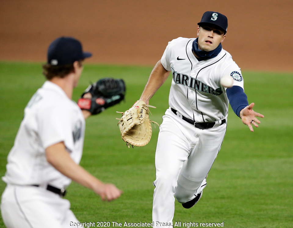 Seattle Mariners first baseman Evan White to pitcher Joey Gerber forcing out Texas Rangers' Nick Solak during the seventh inning of a baseball game, Saturday, Aug. 22, 2020, in Seattle. (AP Photo/John Froschauer)