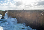 Large waves crash into the coastal cliffs at Loch Ard Gorge on the Great Ocean Road in Victoria, Australia