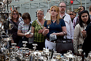 Punters at a silverware stall on Portobello Road market, Notting Hill, West London. This famous Sunday market is when the antique stalls come out as well as the food stalls.