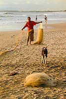 Bali, Badung, Kuta. A fisherman prepares his net on Kuta Beach.