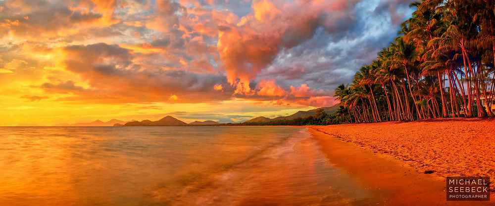 A panoramic photograph of sunrise looking south along the beach at Palm Cove, with low scattered cumulus clouds lit up by the early morning sun.<br /> <br /> Limited Edition of 125