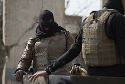 Licensed to London News Pictures. 13/02/2017. Mosul, Iraq. A masked National Security Service officer stands in the back of a pickup truck as his team prepares to leave a base in eastern Mosul to raid the homes of suspected ISIS members in the city.<br /> <br /> The Jihaz Al-Amin Al-Watani, roughly translated as the National Security Service or NSS, are a secretive Iraqi agency that works under the responsibility of the Ministry of Interior. Since the liberation of eastern Mosul in January 2017 the NSS have been actively hunting down ISIS members who stayed behind to continue terrorism as part of sleeper cells and residents who worked with the group during its two year occupation. Recruiting from across the country agency is responsible for internal security inside Iraq and has a broad remit to investigate and arrest everything from terrorists and foreign spies to financial criminals and drug traffickers.<br /> <br /> The Jihaz Al-Amin Al-Watani, roughly translated as the National Security Service or NSS, are a secretive Iraqi agency that works under the responsibility of the Ministry of Interior. Since the liberation of eastern Mosul in January 2017 the NSS have been actively hunting down ISIS members who stayed behind to continue terrorism as part of sleeper cells and residents who worked with the group during its two year occupation. Recruiting from across the country agency is responsible for internal security inside Iraq and has a broad remit to investigate and arrest everything from terrorists and foreign spies to financial criminals and drug traffickers. Photo credit: Matt Cetti-Roberts/LNP