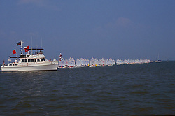 Stock photo of sailboats lined up on the water ready to start the race