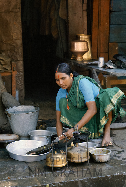 Indian woman preparing a meal in her pavement home, India