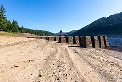 © Licensed to London News Pictures. 05/07/2018. Upper Derwent Valley UK. Scenes this morning at Derwent Reservoir in Derbyshire show the extent the water level has dropped during the UK heatwave leaving a old construction railway bridge visible on the shoreline. Photo credit: Andrew McCaren/LNP