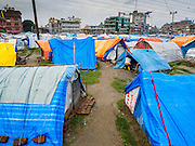 05 AUGUST 2015 - KATHMANDU, NEPAL: The large Internal Displaced Person (IDP) Camp in the center of Kathmandu. The camp is next to one the most expensive international hotels in Kathmandu. More than 7,100 people displaced by the Nepal earthquake in April live in 1,800 tents spread across the space of three football fields. There is no electricity in the camp. International NGOs provide water and dug latrines on the edge of the camp but the domestic waste water, from people doing laundry or dishes, runs between the tents. Most of the ground in the camp is muddy from the running water and frequent rain. Most of the camp's residents come from the mountains in northern Nepal, 8 - 12 hours from Kathmandu. The residents don't get rations or food assistance so every day many of them walk the streets of Kathmandu looking for day work.    PHOTO BY JACK KURTZ