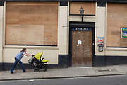Woman pushes a pram past a closed down boarded up pub. Signs of the continued economic downturn and recession as many small businesses struggle to remain open.