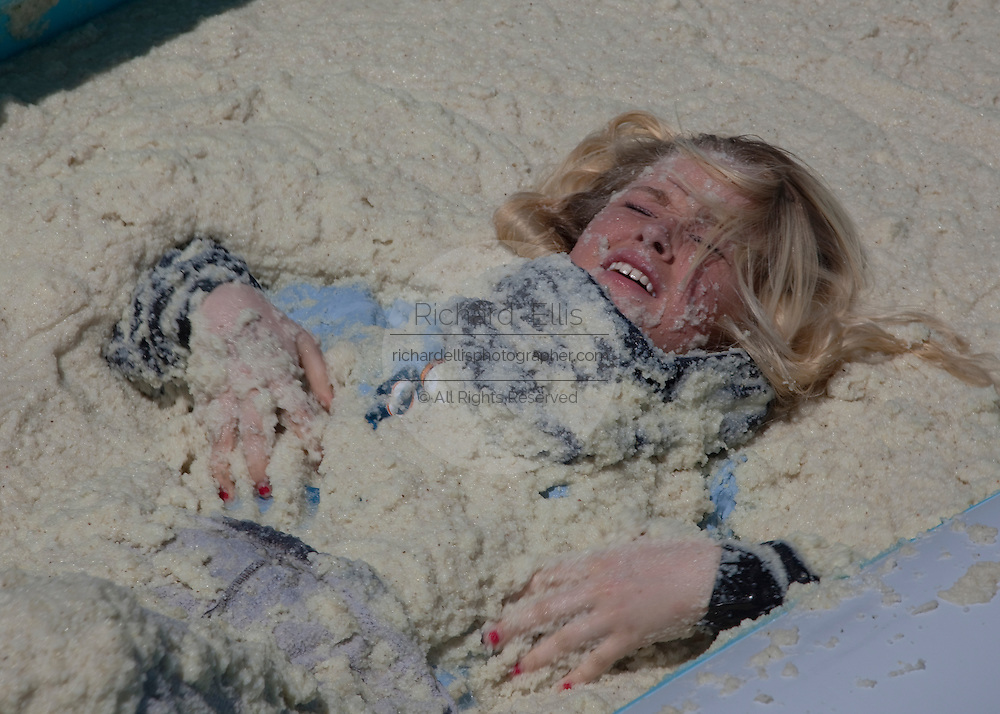 ST GEORGE, SC - APRIL 18: Clarrisa Lippert reacts as he rolls around in a giant vat of grits April 18, 2009 during the World Grits Festival in St. George, SC. The contest is won by having the most grits stick to your body.     (Photo Richard Ellis)