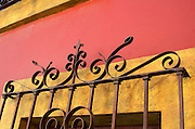 Ornate security grille over colorful plasterwork, Oaxaca, Mexico.