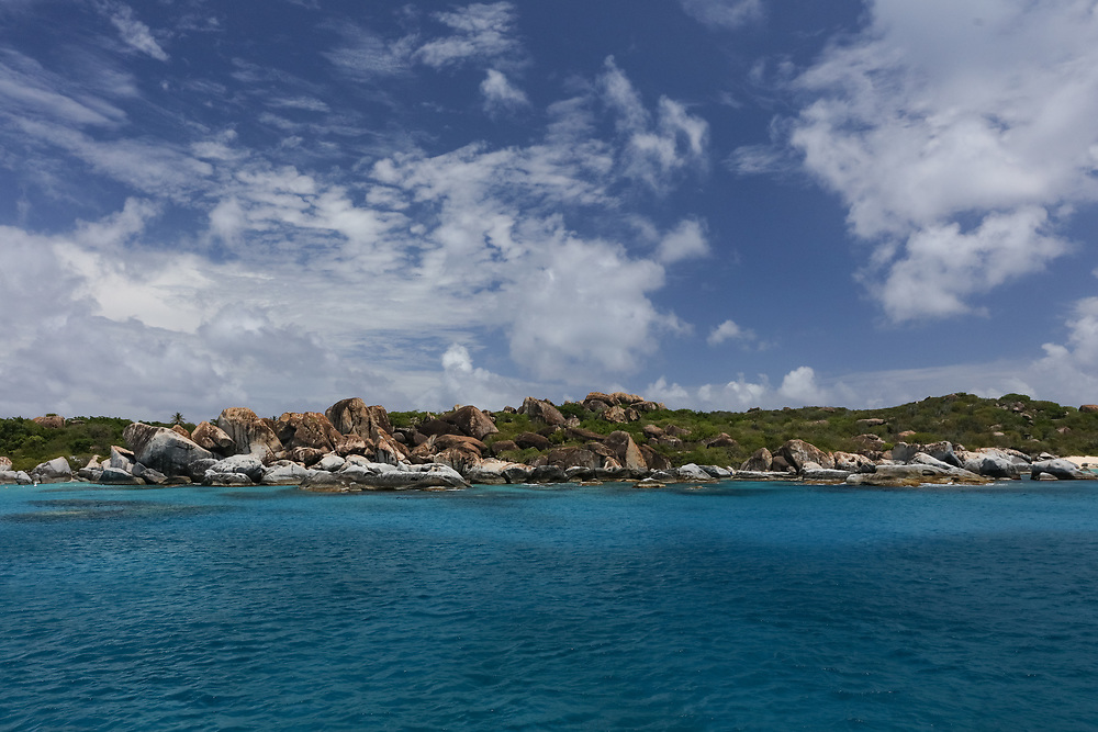A view of The Baths from a sailboat in the blue waters of the BVI's.