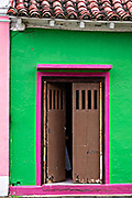 A doorway of a colorful colonnade style building in Tlacotalpan, Veracruz, Mexico. The tiny town is painted a riot of colors and features well preserved colonial Caribbean architectural style dating from the mid-16th-century.