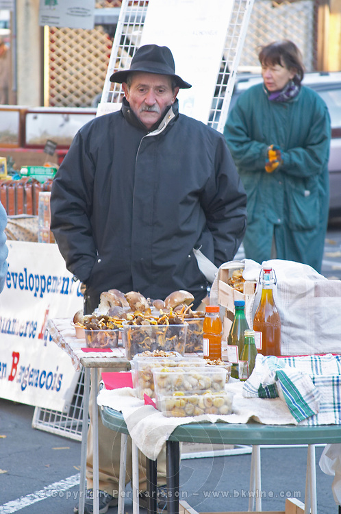 A man in a hat selling mushrooms at a market stall. Bergerac Dordogne France
