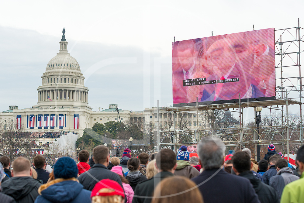 Washington DC, United States - A video transition of Donald J. Trump and Barack Obama can be seen on the Jumbotron, as both close their eyes in prayer during Trump's 2017 inauguration ceremony.